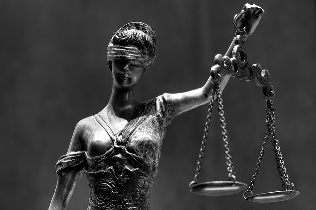 Black and white photo of blind justice statue holding scales