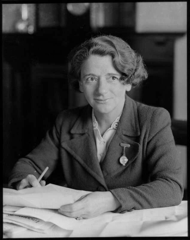 Black and white photo of Ellen Wilkinson working with documents